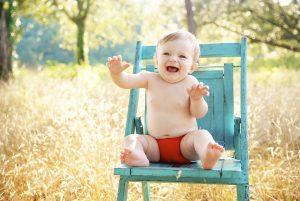"alt=""bambino seduto su sedia azzurra ride"""
