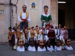 """alt=""""persone in costume tradizionale davanti a due giganti"""""""